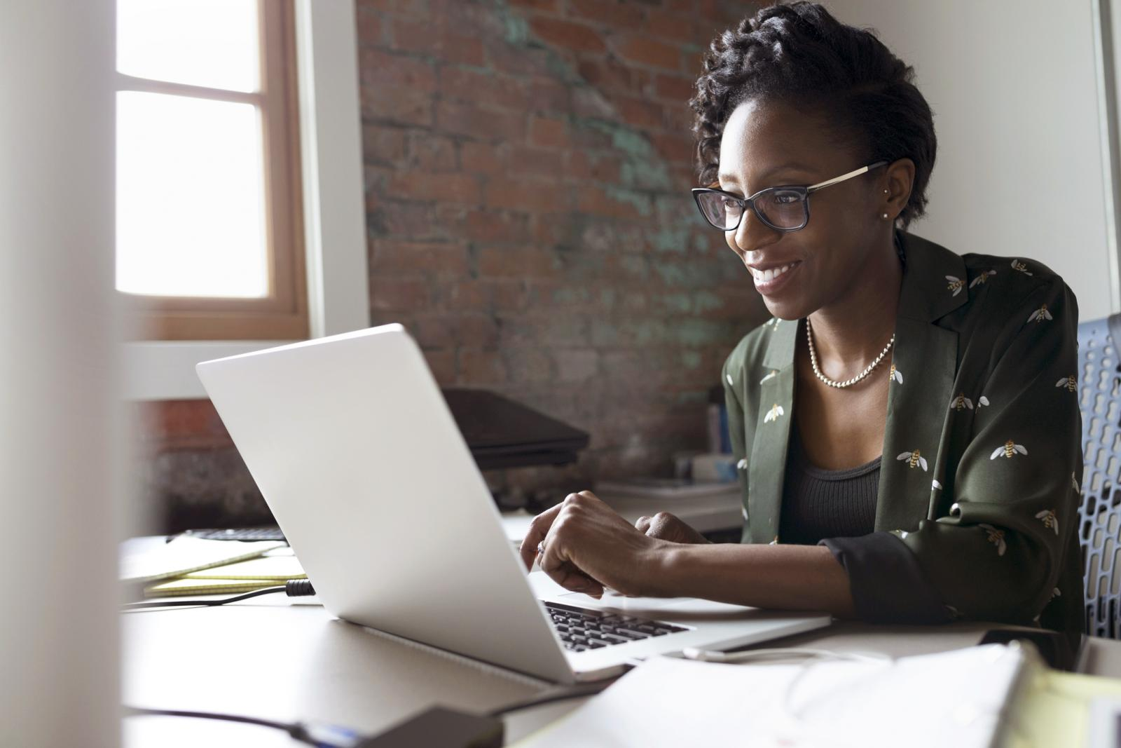 Smiling creative businesswoman working at laptop