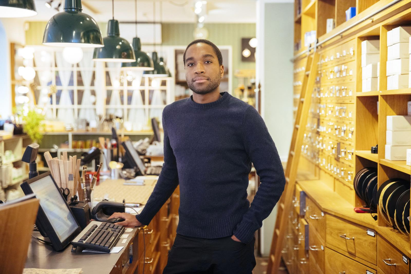Confident young male entrepreneur standing behind store counter
