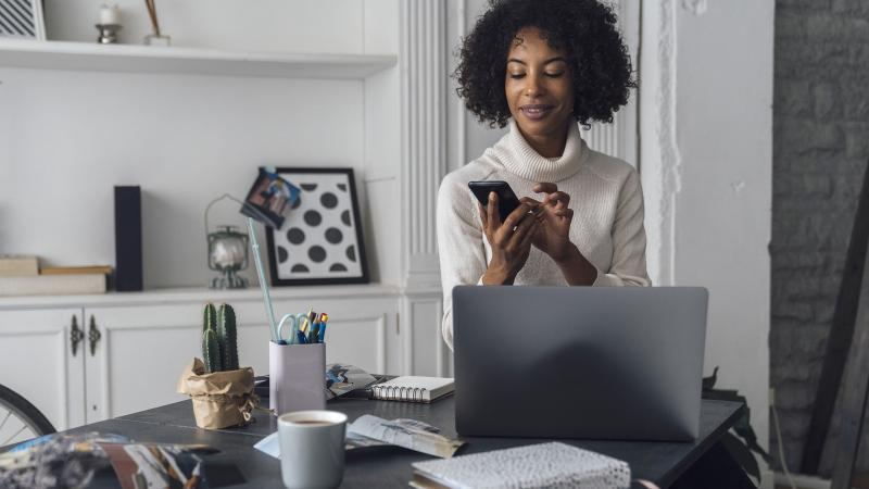 Woman working in her home office, using smart phone