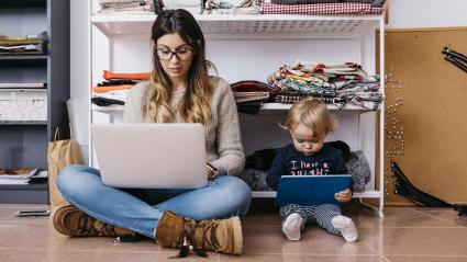 Mother and young daughter sitting on the floor at home using laptop and tablet