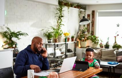 Father working with son watching tablet