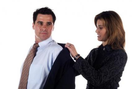 Wife helping husband put on suit coat