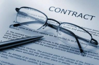 Glasses and pen laying on a business contract