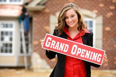 Woman Holding Grand Opening Sign