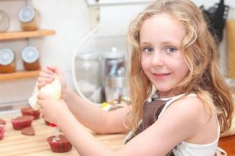 Girl decorating Christmas cupcakes