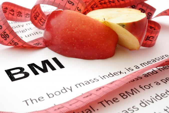 Apple slices and measuring tape on BMI article