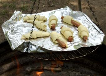 Pigs in a blanket cooking over a campfire