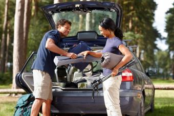 Couple unpacking their car on camp site