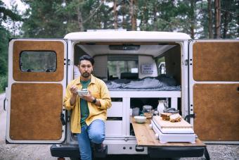Man eating breakfast next to his camper van