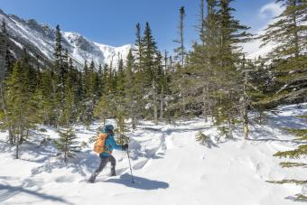 A young woman hiking on a sunny, snowy winter day in the White Mountains of New Hampshire