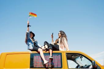 https://www.gettyimages.com/detail/photo/two-women-sitting-on-roof-of-van-waving-pride-flag-royalty-free-image/1266030311?adppopup=true