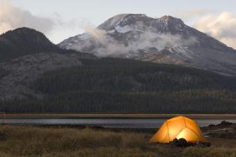 Illuminated tent by lake in mountains