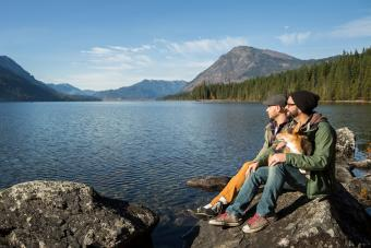 couple and their dog sit and enjoy Lake Wenatchee.