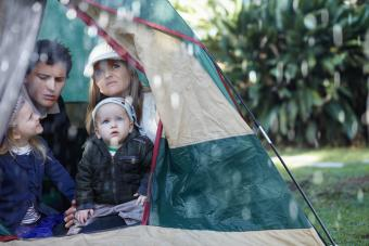 family stuck in their tent during a rainy day