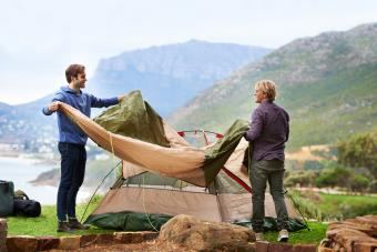 Two men setting up their campsite