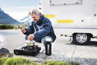 man cooking on turist stove nearby campervan in mounatins