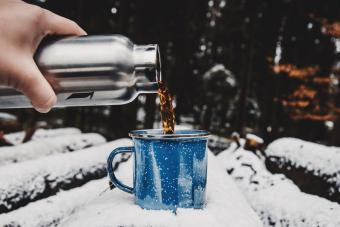 Cropped Hand Pouring Tea In Cup On Snow Covered Log