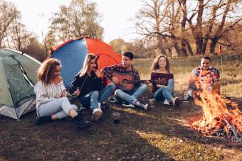 Multi ethnic group of friends camping by the fire