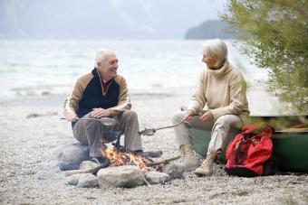Senior couple sitting at campfire, grilling fish