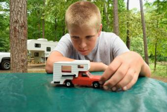 Young boy playing with pickup camper toy in campground