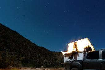 Woman looking up at a scenic desert sky on her camper truck