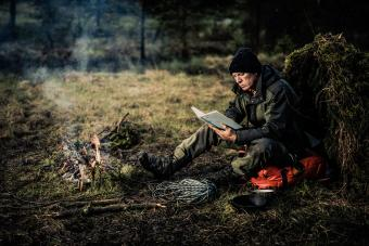 Man reading book in forest