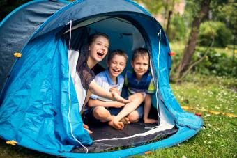 Kids happily sitting inside of blue tent