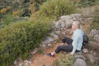 Woman hiker rests on trail