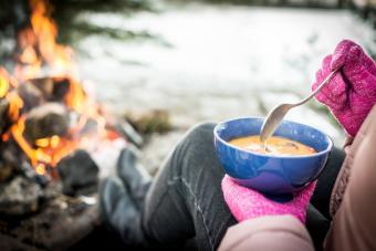 Woman Enjoying Food with Campfire