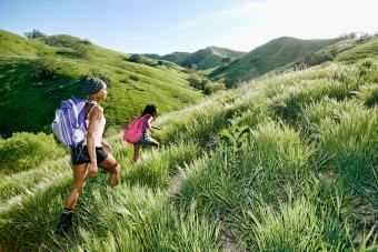 mother and daughter walking on rural hillside