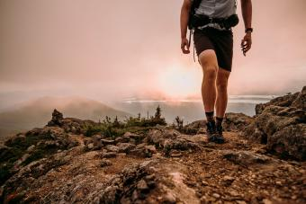Hiker with cell phone walks along Appalachian Trail