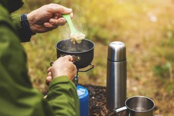 preparing oatmeal porridge outdoors on gas burner