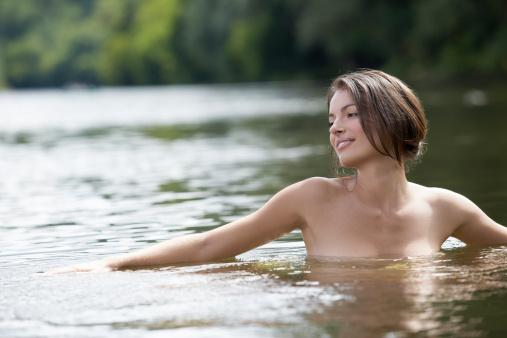 Young woman bathing naked in river