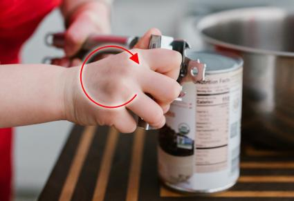 Woman Opening Can with manual can opener