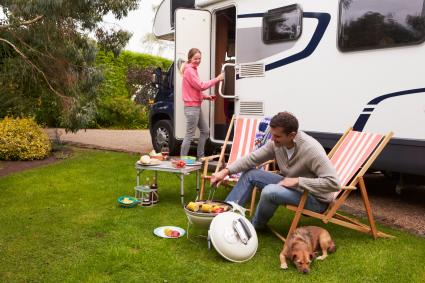 Couple RV Camping and cooking with their dog