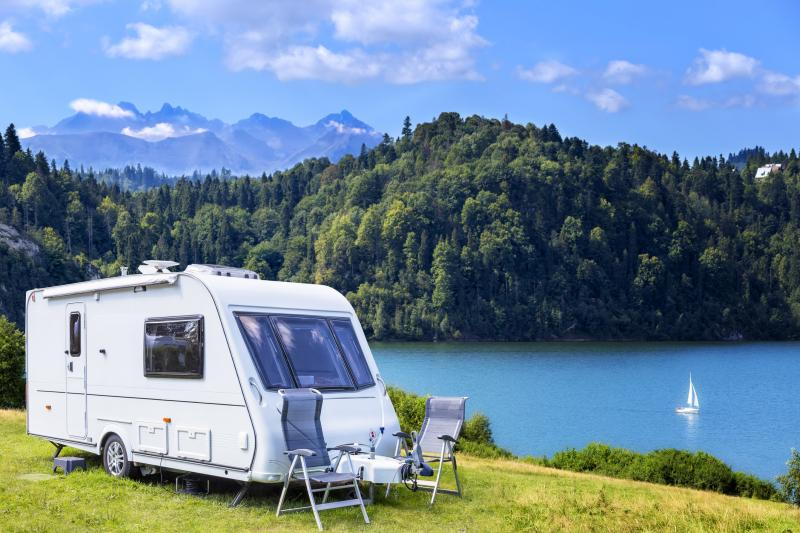 Summer scene with camper trailer by the lake