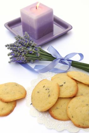 a burning purple candle with cookies