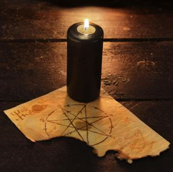 Black candle with pentagram on table