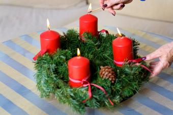 Woman Hand Igniting Advent Candles On Table