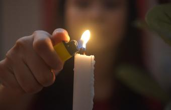 Woman Burning Candle With Lighter