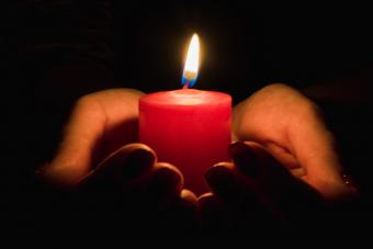 Close-Up Of Hand Holding Red Candle