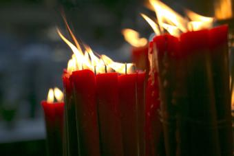 Burning red candle in a draft
