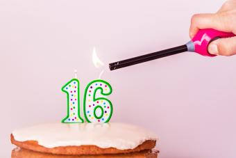 Hand Igniting Candle On Cake
