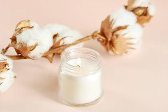A cotton flower and a white candle in a glass jar