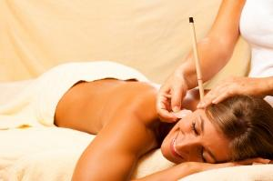 Woman receiving ear candling treatment