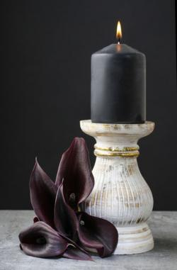 black candle and calla flower