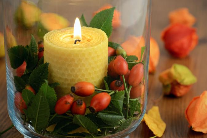 Beeswax candle burning on table