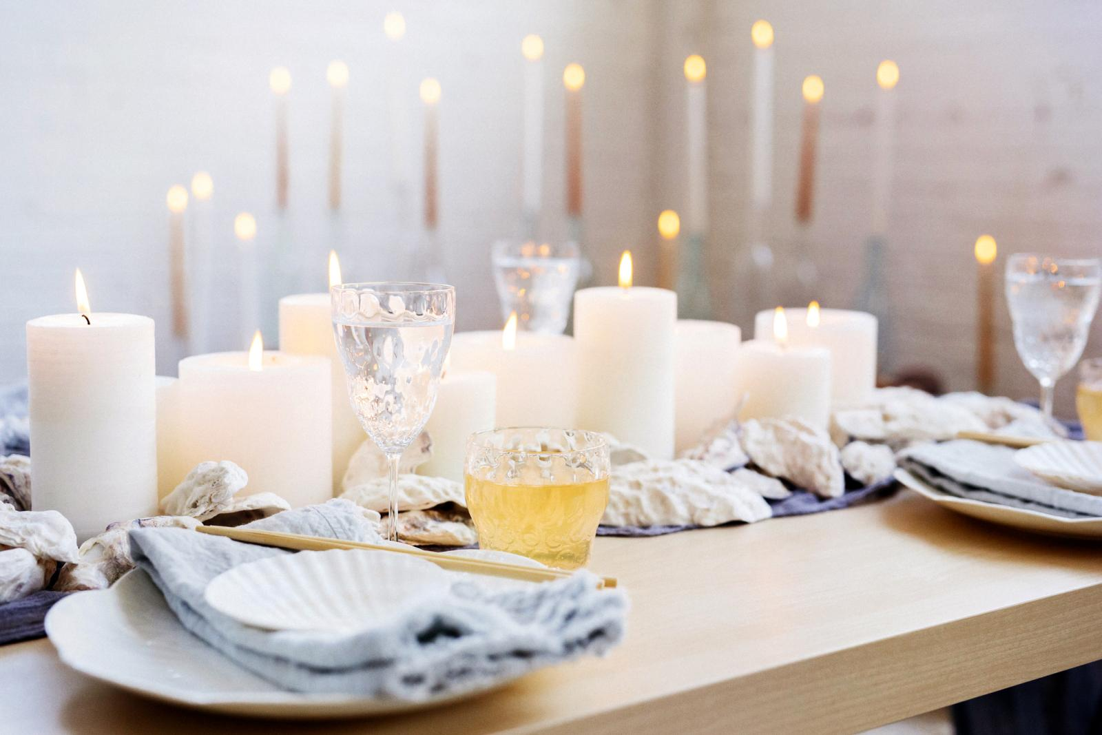 A table with lit candles, china plates and glasses