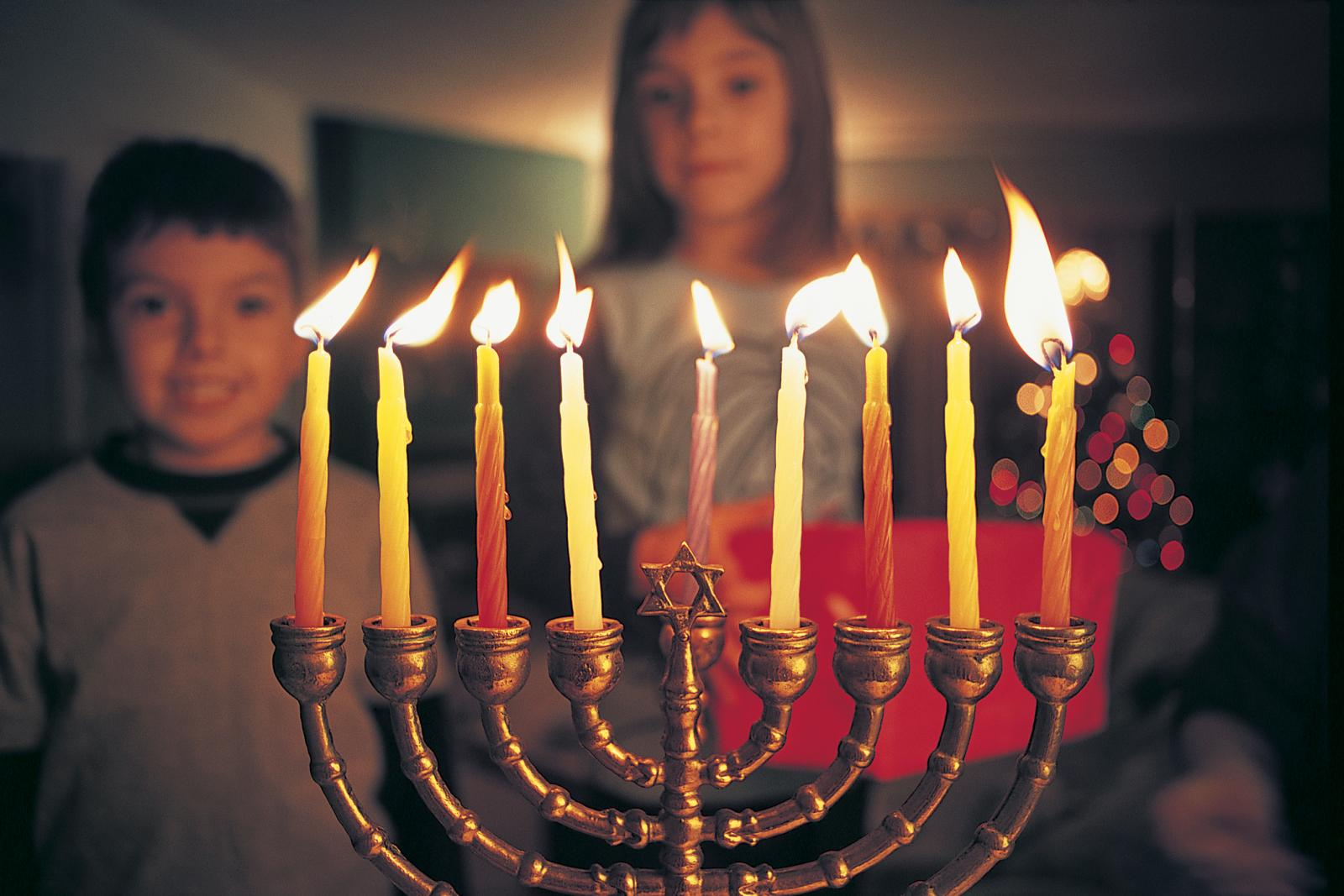 Brother and Sister Watching Candles Burning on a Menorah During Hannukah