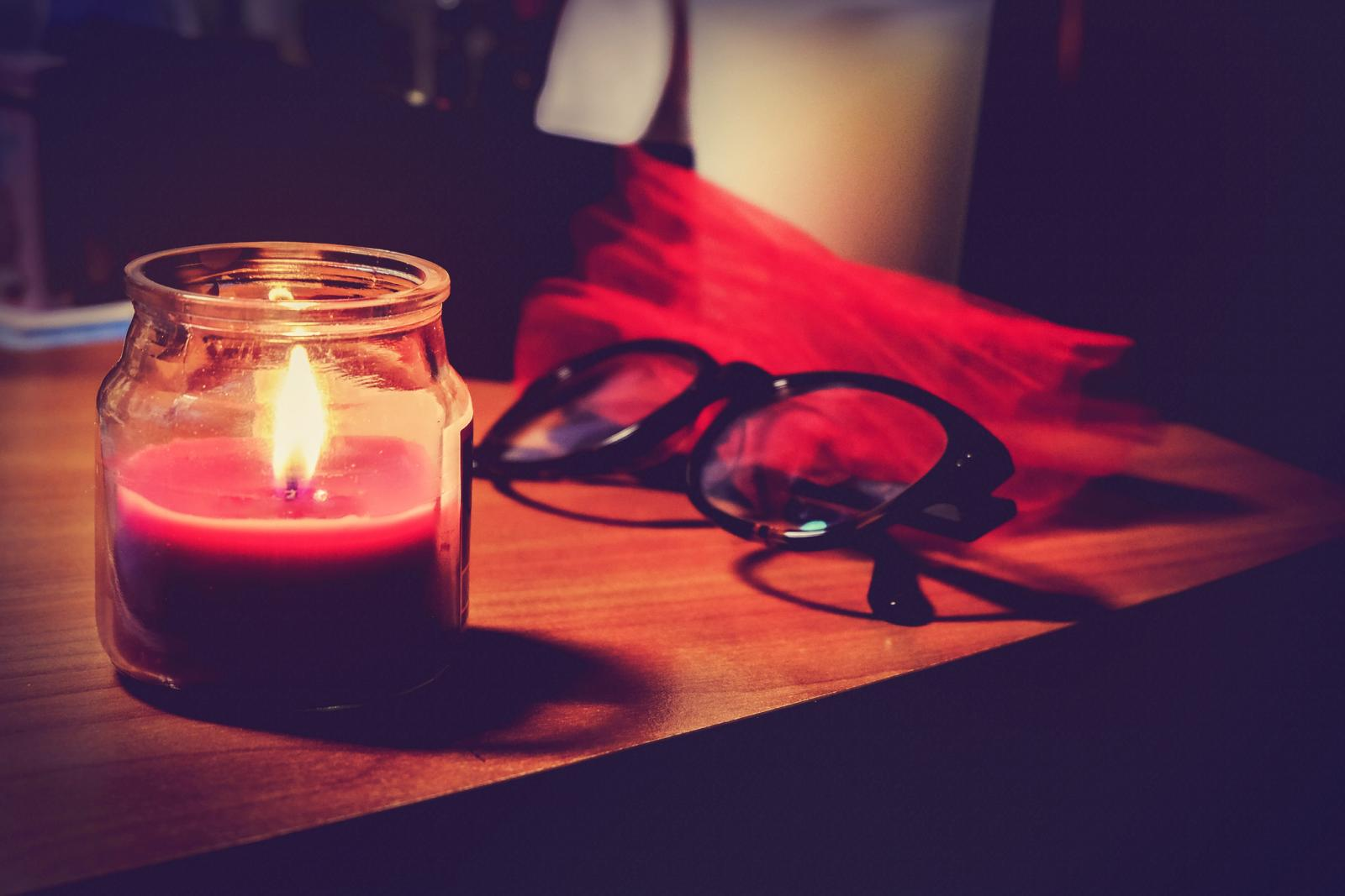 Lit Candle In Jar And Eyeglasses On Table